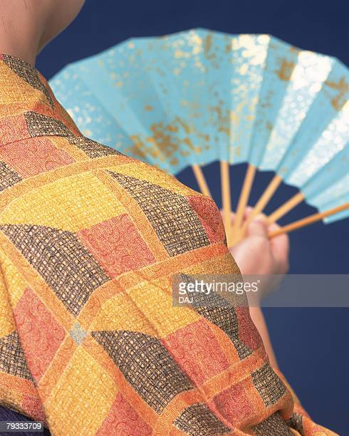 The back of a woman in kimono holding a fan, Close Up
