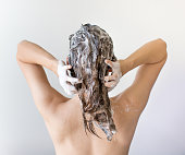 Young woman. Back shot. Hands on back of head. Hair has many suds from shampoo