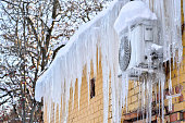 The back of the building is air-conditioned cafe on the wall covered with a thick layer of icicles after a sharp change in weather.