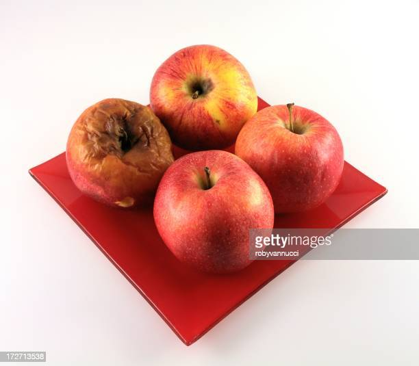 The bad element; four red apples,one is rotten