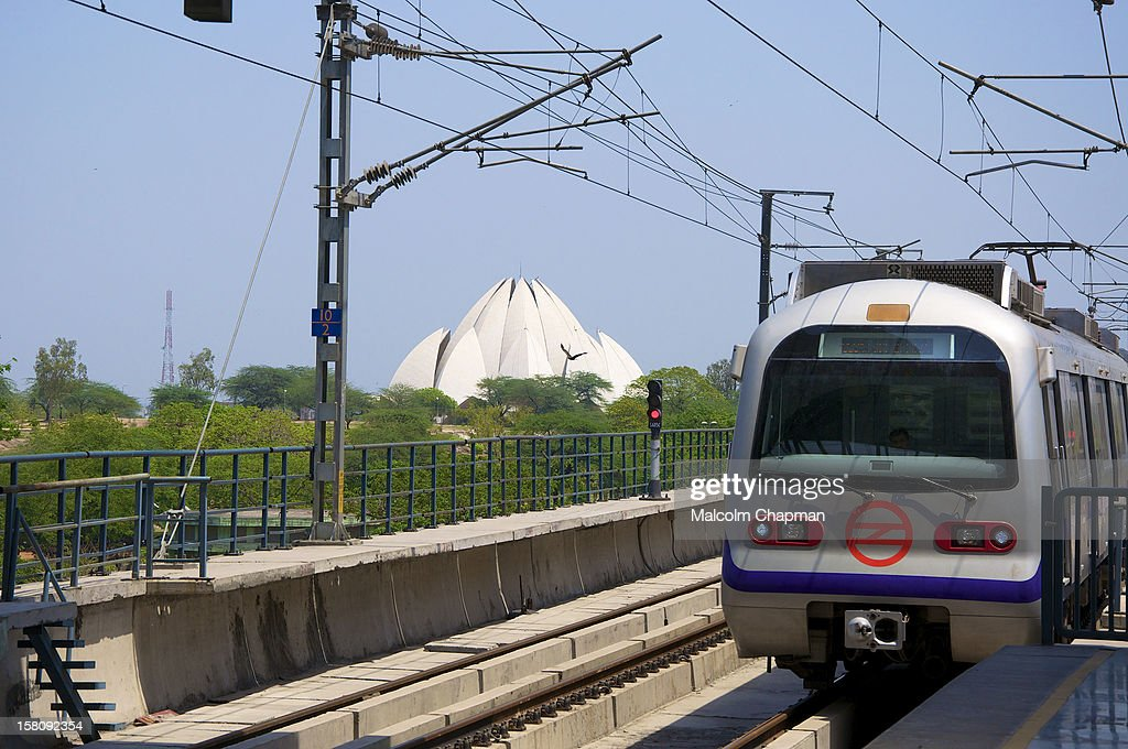 The Bahá'í House of Worship in New Delhi, India, popularly known as the Lotus Temple or Mother Temple seen here from Nehru Place Metro Station. It is one of many Bahai House temples around the world. This Baha'i temple was designed by architect Fariborz Sahba and the structural engineers were Flint & Neill. This is the 'Violet Line' of The Delhi metro (DMRC) between Central Secretariat and Badarpur.
