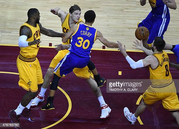 The ball eludes LeBron James of the Cleveland Cavaliers teammates Timofey Mozgov Matthew Dellavedova and Golden State Warriors Stephen Curry during...