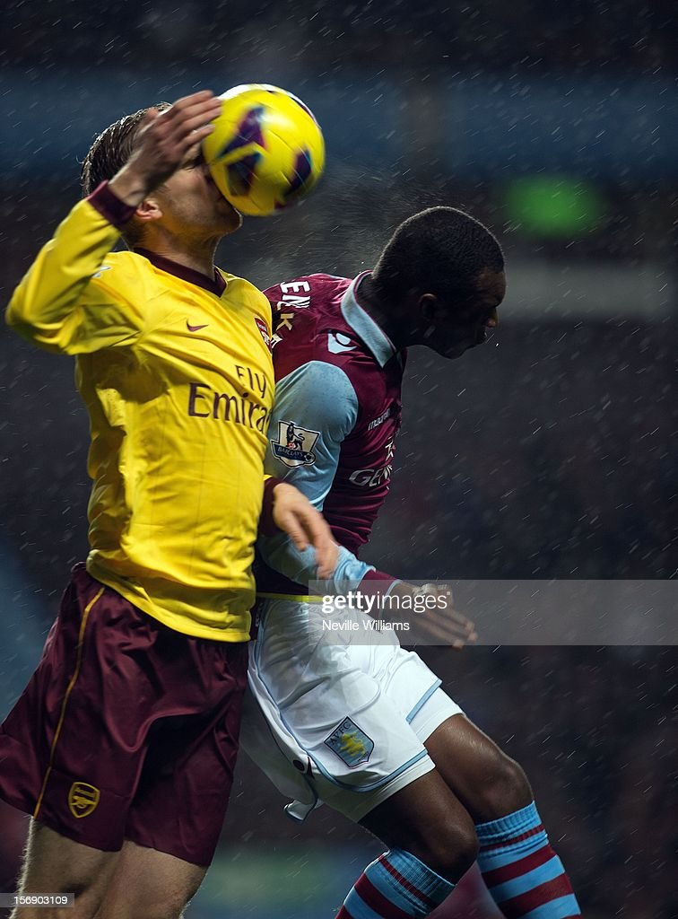 The ball hits Per Mertesacker of Arsenal in the face as he and Christain Benteke of Aston Villa jump for a header during the Barclays Premier League match between Aston Villa and Arsenal at Villa Park on November 24, 2012 in Birmingham, England.