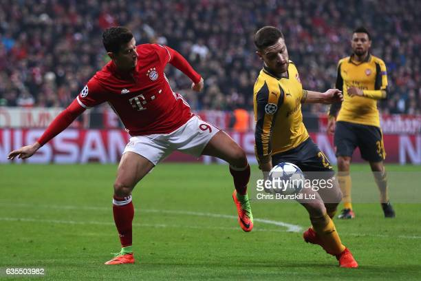 The ball hits the hand of Shkodran Mustafi of Arsenal as he competes with Robert Lewandowski of Bayern Munich during the UEFA Champions League Round...