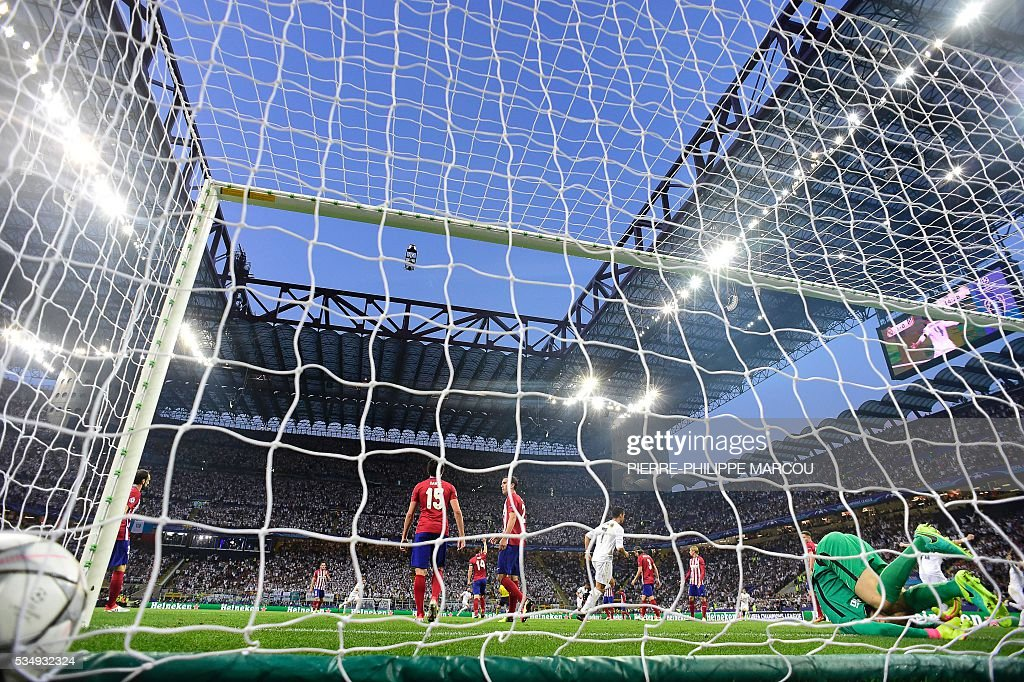 The ball is seen in the net after Real Madrid's Spanish defender Sergio Ramos scored the opening goal during the UEFA Champions League final football match between Real Madrid and Atletico Madrid at San Siro Stadium in Milan, on May 28, 2016. / AFP / PIERRE