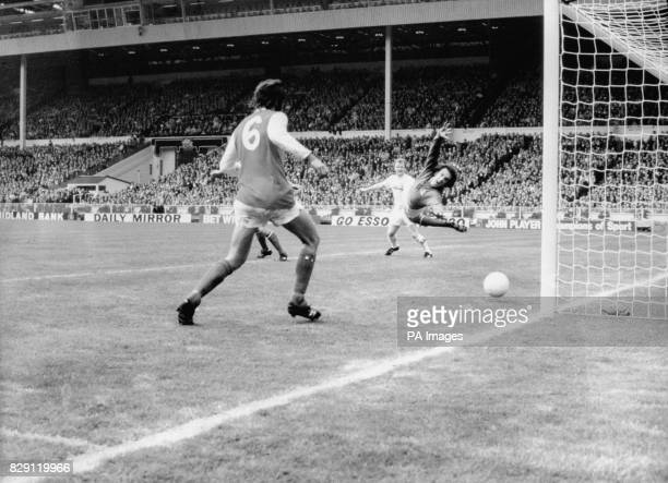 The ball is seen on its way to the net as Leeds United scored their one decisive goal in the Cup Final at Wembley Leeds' captain Billy Bremner looks...