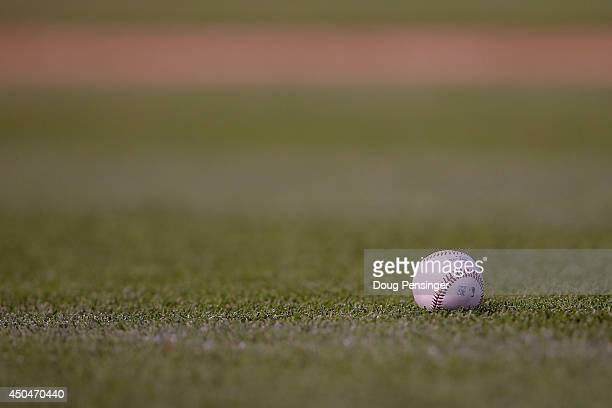 The ball lies on the grass as the Atlanta Braves face the Colorado Rockies at Coors Field on June 11 2014 in Denver Colorado