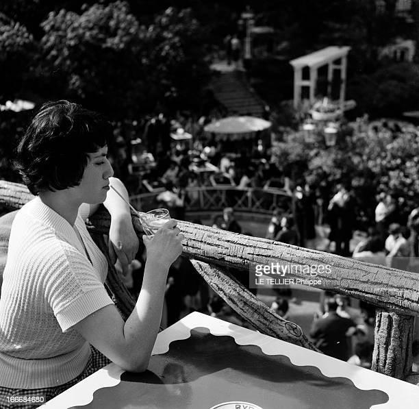 The Ball Of The Fiances En juin 1955 en France une jeune femme avec une boisson gazeuse à la main sur une terrasse regardant des couples danser lors...