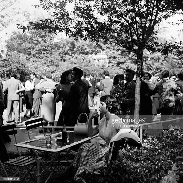 The Ball Of The Fiances En juin 1955 en France une jeune femme avec une boisson gazeuse à la main assise à une table regardant des couples danser...