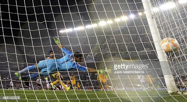 The ball reaches the net after Argentina's River Plate forward Lucas Alario scores the team's first goal against Mexico's Tigres goalkeeper Nahuel...