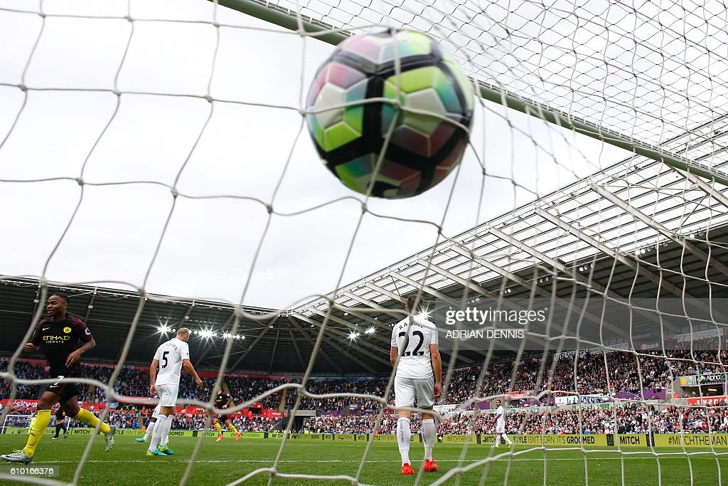 The ball slams into the back of the net after Manchester City's Argentinian striker Sergio Aguero scored his first goal during the English Premier League football match between Swansea City and Manchester City at The Liberty Stadium in Swansea, south Wales on September 24, 2016. / AFP / Adrian DENNIS / RESTRICTED TO EDITORIAL USE. No use with unauthorized audio, video, data, fixture lists, club/league logos or 'live' services. Online in-match use limited to 75 images, no video emulation. No use in betting, games or single club/league/player publications. /