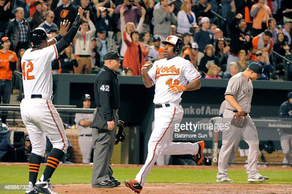 The Baltimore Orioles' Adam Jones left welcomes Delmon Young who scored on a double by Chris Davis off New York Yankees relief pitcher Justin Wilson...