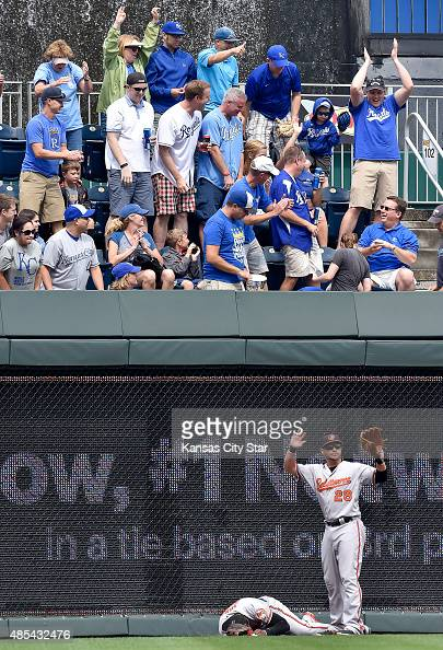 The Baltimore Orioles' Steve Pearce signals for help after center fielder Adam Jones ran into the wall chasing a ground rule double by the Kansas...