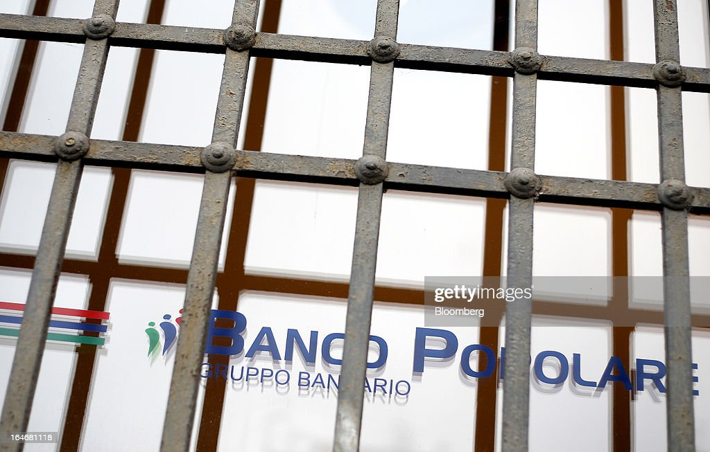 The Banco Popolare SC logo is displayed on a window outside the company's headquarters in Verona, Italy, on Monday, March 25, 2013. Italy's economy remains mired in its longest recession in two decades and a month-old political impasse threatens to increase sovereign-debt yields and bank funding costs. Photographer Alessia Pierdomenico/Bloomberg via Getty Images