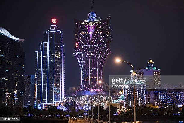 The Bank of China Ltd building second left and Casino Grand Lisboa operated by SJM Holdings Ltd center stand illuminated at night in Macau China on...