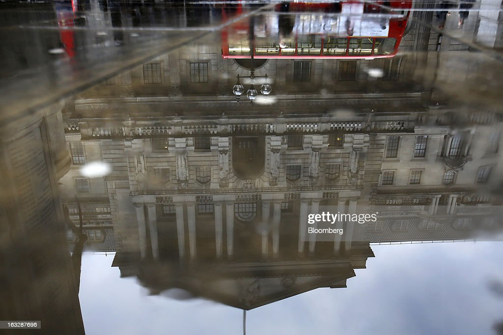 The Bank of England (BoE) is reflected in a puddle on a sidewalk in London, U.K., on Thursday, March 7, 2013. The pound dropped to its weakest level in more than 2 1/2 years versus the dollar before Bank of England policy makers announce their decision on whether they will add more stimulus to boost the U.K. economy. Photographer: Simon Dawson/Bloomberg via Getty Images