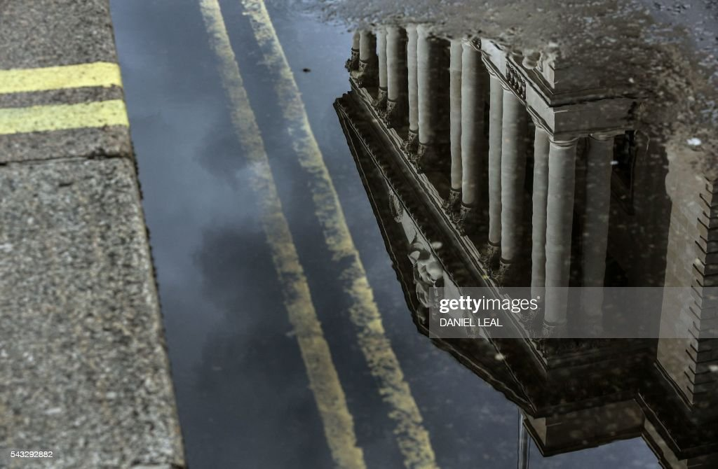 The Bank of England is reflected in puddle of rain water in the City of London on June 27, 2016. Britain should only trigger Article 50 to leave the EU when it has a 'clear view' of how its future in the bloc looks, finance minister George Osborne said Monday following last week's shock referendum. London stocks extended their losses in early afternoon Monday, led by banking, airline and property shares, following Britain's vote to leave the EU. / AFP / Daniel Leal-Olivas