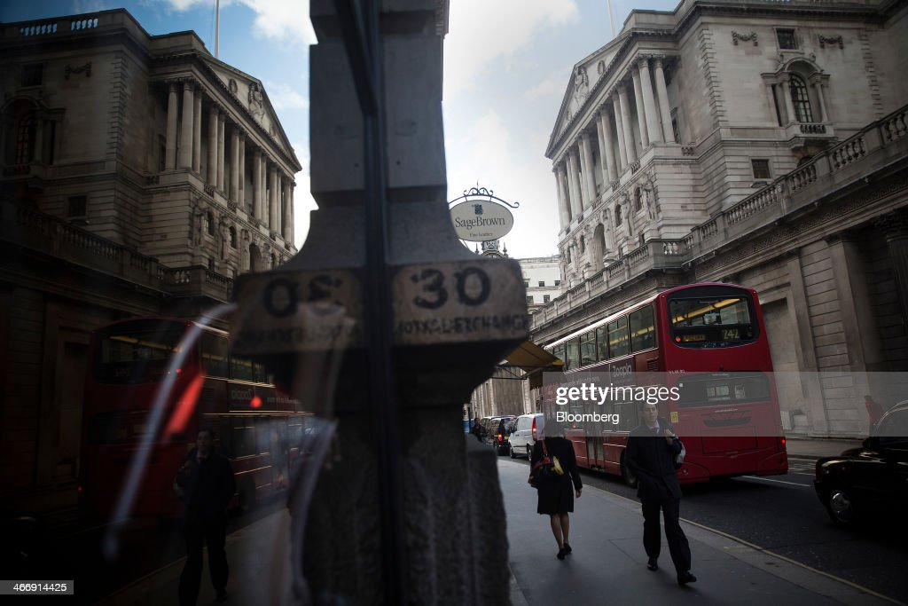 The Bank of England is reflected in the window of a store on Threadneedle Street in London, U.K., on Tuesday, Feb. 4, 2014. Between 2007 and 2011, policy makers in London lagged behind their American counterparts in cutting rates and adopting emergency policy measures in response to the financial crisis. Photographer: Simon Dawson/Bloomberg via Getty Images