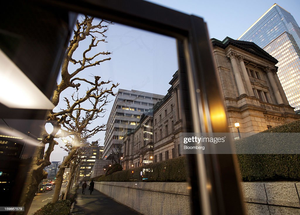 The Bank of Japan headquarters stands at dusk, seen through the window of a pay phone booth, in Tokyo, Japan, on Tuesday, Jan. 22, 2013. The Bank of Japan set a 2 percent inflation target and said it will shift to Federal Reserve-style open-ended asset purchases in its strongest commitment yet to ending two decades of deflation. Photographer: Tomohiro Ohsumi/Bloomberg via Getty Images