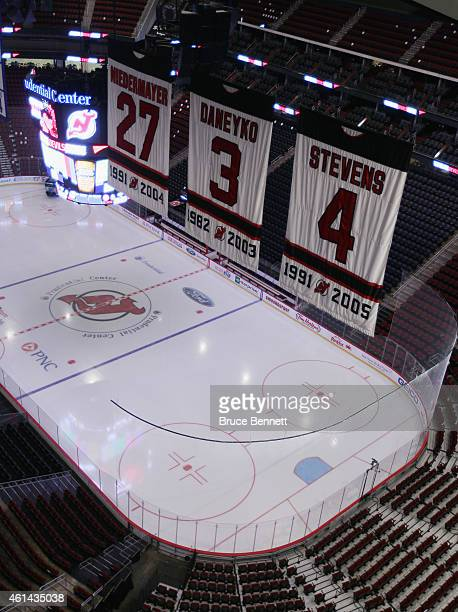 The banners for Scott Niedermayer Ken Daneyko and Scott Stevens hang over the ice prior to the game between the New Jersey Devils and the New York...