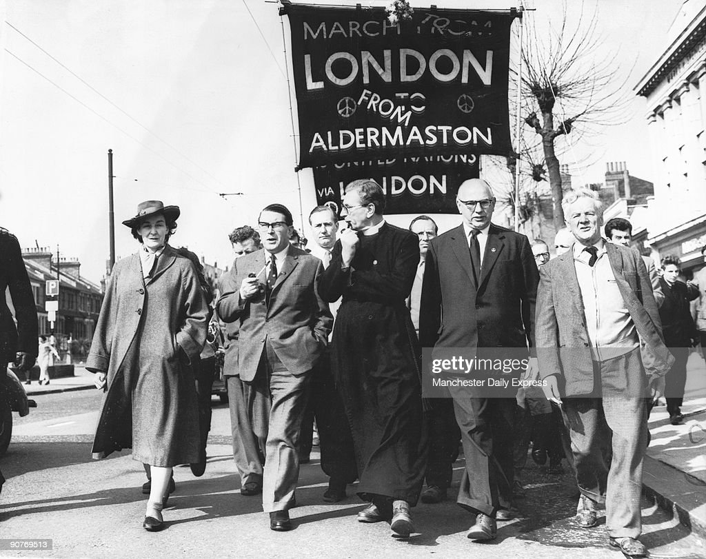 �The Ban-the-Bomb Aldermaston march set out this morning from Chiswick on its way to Hyde Park.� The original London-Aldermaston banner has been adapted. L-R: Jacquetta Hawkes, Professor Calder, Canon Collins, Frank Cousins and Emrys Hughes. Aldermaston in Berkshire became a nuclear base in 1950. The Campaign for Nuclear Disarmament (CND), was launched by the philosopher Bertrand Russell and Canon John Collins (centre) and annual marches from Aldermaston to London followed. Aldermaston is the headquarters of the Atomic Weapons Establishment (AWE) where Trident submarine-launched nuclear intercontinental ballistic missiles are made. It has close links with nuclear weapons laboratories in the United States. CND still campaigns against the base's activities.