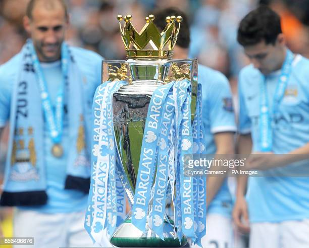 The Barclays Premier League trophy is seen in front of Manchester City's Pablo Zabaleta Samir Nasri and Jesus Navas