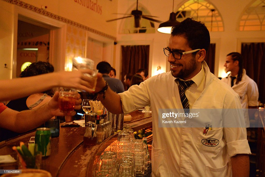The barman in Joe Penas bar says cheers to customers while having a drink in his hand in this downtown bar in Gemmayze, on July 18, 2013 in Beirut, Lebanon. Despite the rising tensions between different Muslim factions in the country people enjoy their leisure time and continue their daily life as normal.