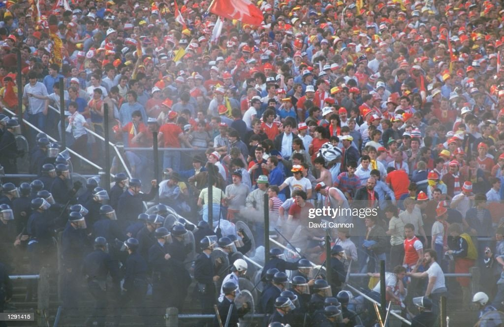 The barriers collapse as supporters try to get on to the pitch during the European Cup Final between Liverpool and Juventus at the Heysel Stadium in...