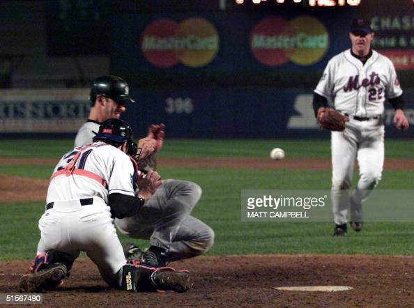The baseball bounces off New York Yankees Jorge Posada allowing the Yankees' clinching goahead run against the New York Mets as catcher Mike Piazza...
