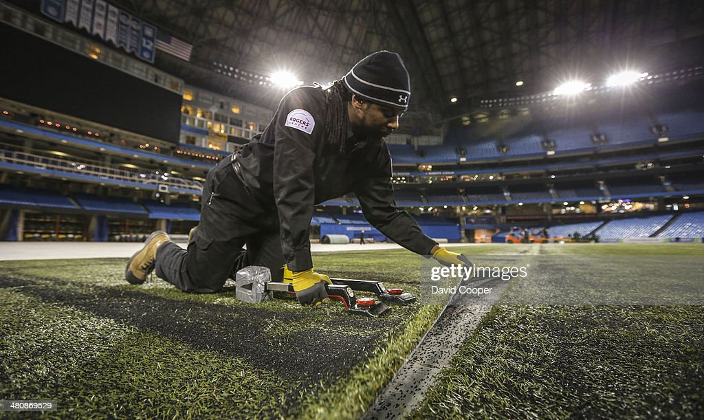 TORONTO, ON- MARCH 26 - The Baseball Turf is going back in at the Rogers Centre over the next two days. Field conversion technicians Mark Wade adjusts the seam between the carpets to get them just right. Let Spring really begin at the Rogers Centre March 26, 2014.
