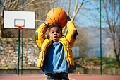 Cute little boy holding a basket ball trying make a score