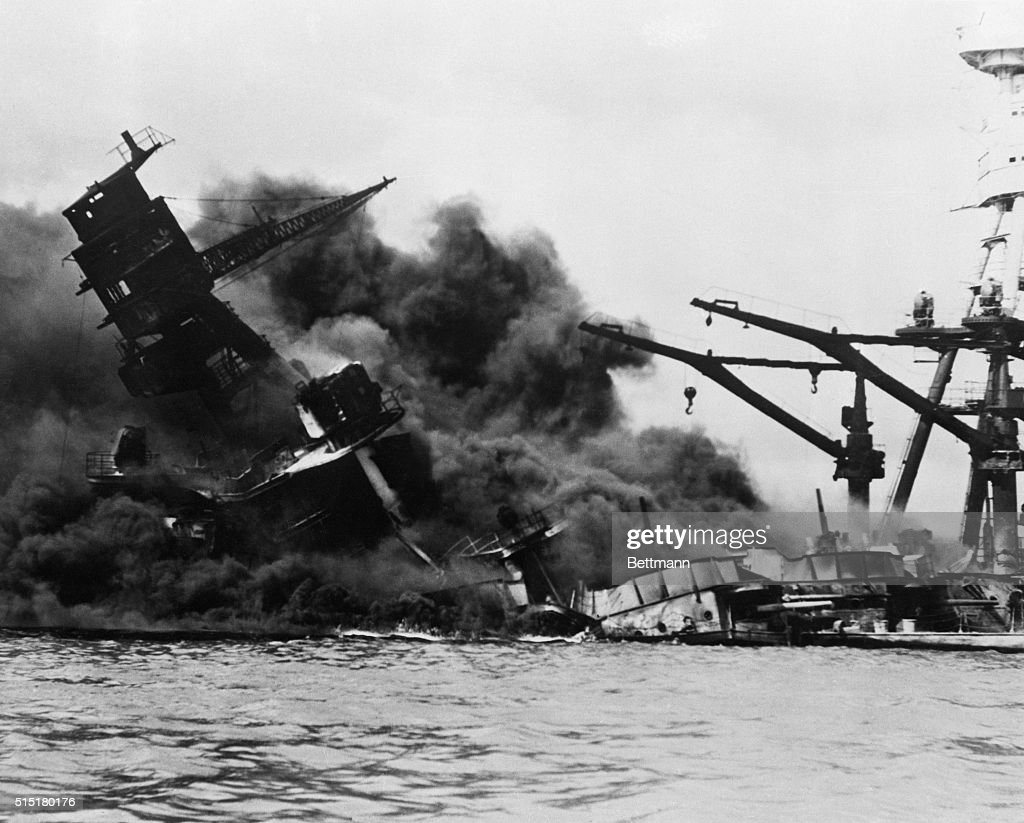 The battleship USS Arizona sinks into Pearl Harbor after being bombed by Japanese planes