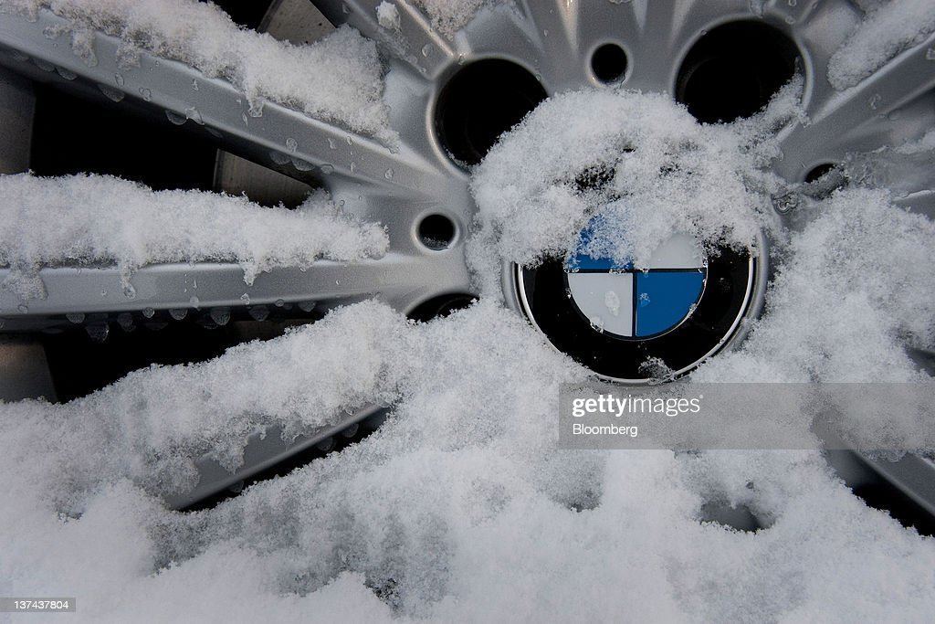 The Bayerische Motoren Werke AG (BMW) logo on the hubcap of a display vehicle is covered with snow at the annual Klosters Snow Polo event in Klosters, Switzerland, on Friday, Jan. 20, 2012. German Chancellor Angela Merkel will open next week's World Economic Forum in Davos, Switzerland, which will be attended by policy makers and business leaders including U.S. Treasury Secretary Timothy F. Geithner. Photographer: Scott Eells/Bloomberg via Getty Images