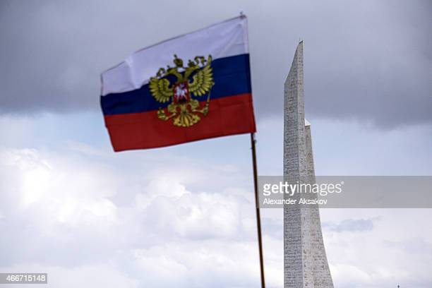 The Bayonet Sail Obelisk is seen with a Russian flag in front as people celebrate the first anniversary of the signing of the decree on the...