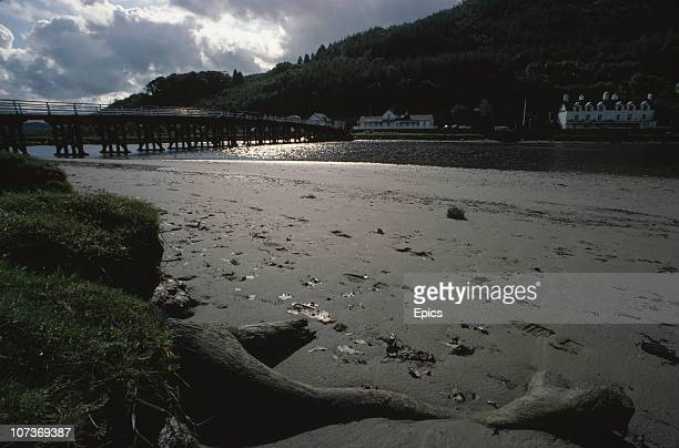 The beach and toll bridge at the village of Penmaenpool Dolgellau Wales September 1982 The wooden tollbridge which crosses the River Mawddach was...