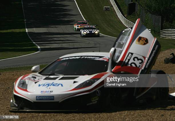 The Beachdeam AMR Aston Martin Vantage GT3 driven by Andrew Howard and Jonny Adam approaches the crashed United Autosports McLaren MP412C driven by...