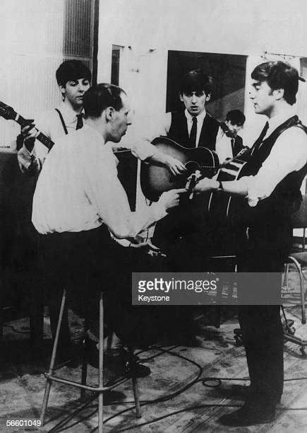 The Beatles at a recording session for the Parlophone label with their producer George Martin circa 1963