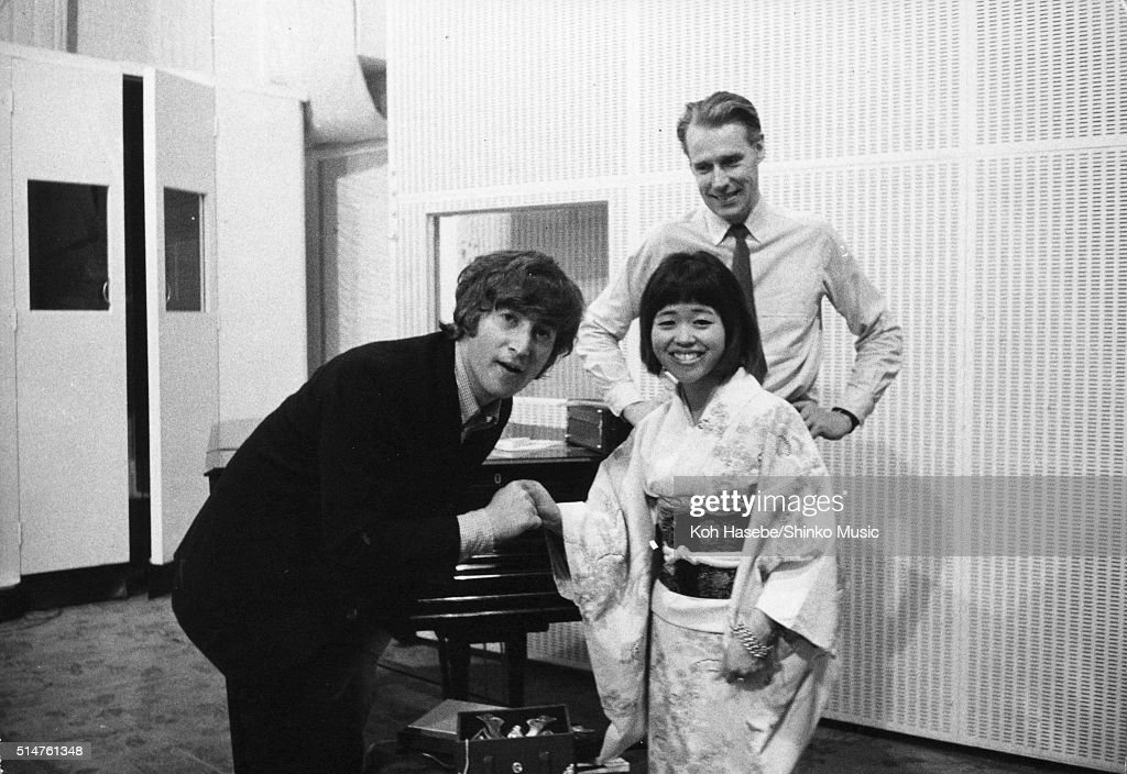 The Beatles at EMI Studios, Abbey Road, London during the recording session for 'It's Only Love', June 15, 1965. L-R John Lennon, Japanese music journalist Rumi Hoshika, George Martin.