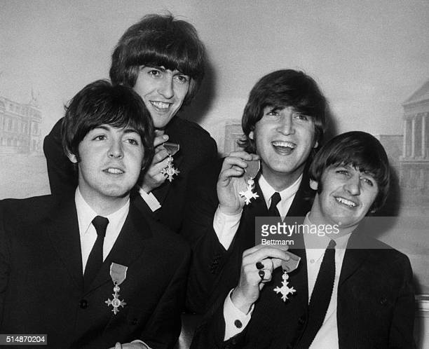 The Beatles display the medals they were awarded when Queen Elizabeth granted them membership in the Order of the British Empire at Buckingham Palace...
