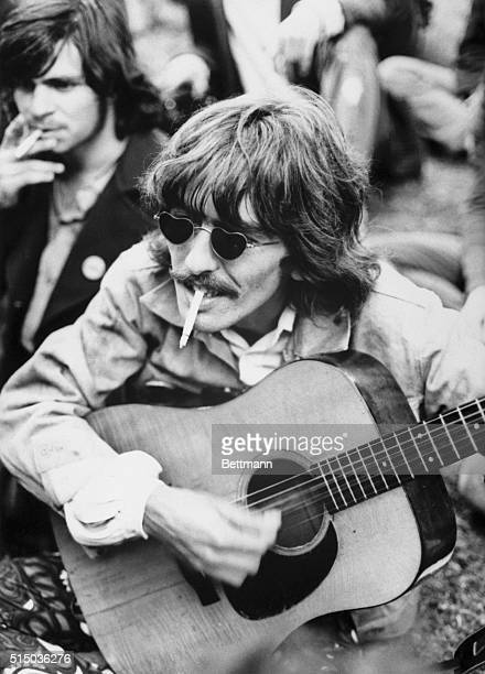 The Beatles lead guitar player George Harrison strums a borrowed guitar as he is followed by local hippies strolling through Golden Gate Park...