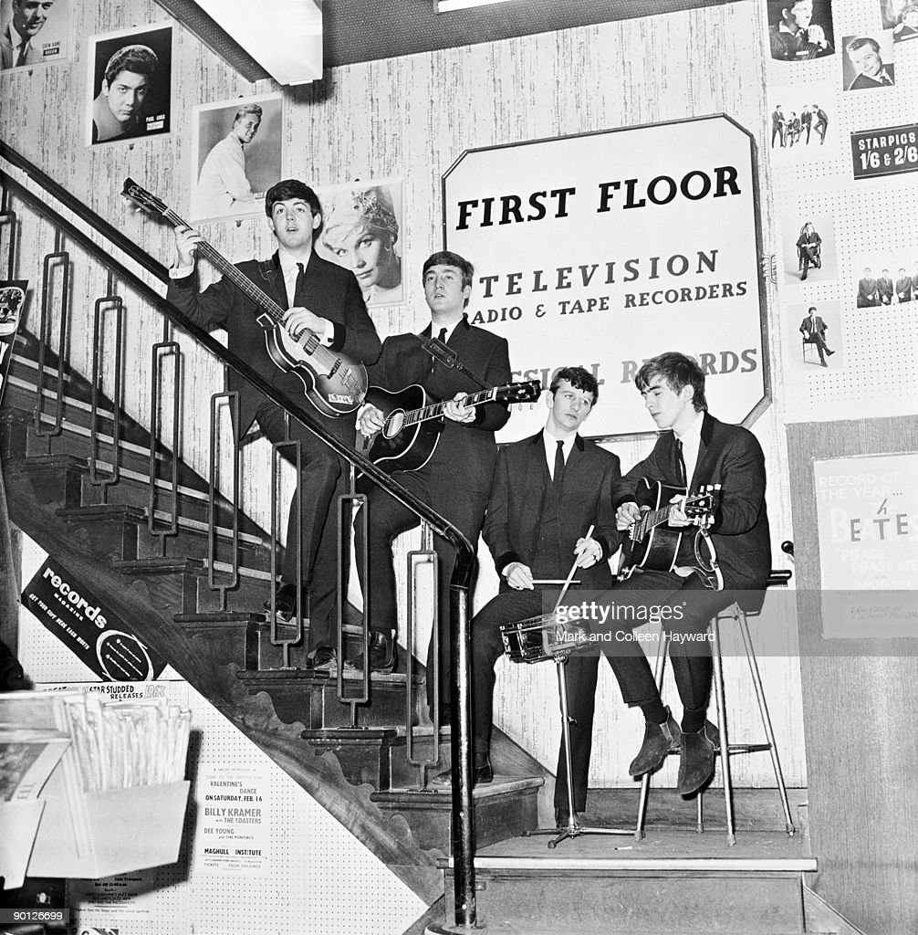 The Beatles pose on the stairs of NEMS (North End Music Stores), Brian Epstein's Liverpool record shop, having just signed a management deal with Brian, 1964.