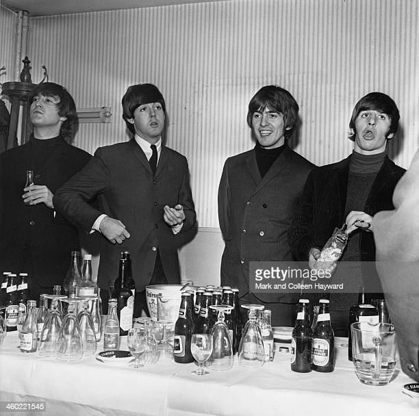 The Beatles posed behind a table of beer bottles and glasses in the United Kingdom circa 1965 Left to right John Lennon Paul McCartney George...