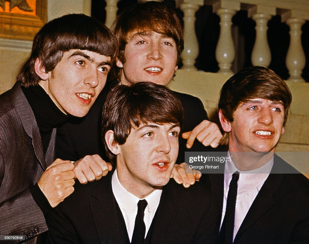 The Beatles smiling together. From left to right: George Harrison, John Lennon (top), Paul McCartney (bottom), and Ringo Starr.