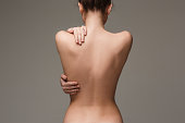 beautiful woman's body on gray background. The nude woman back