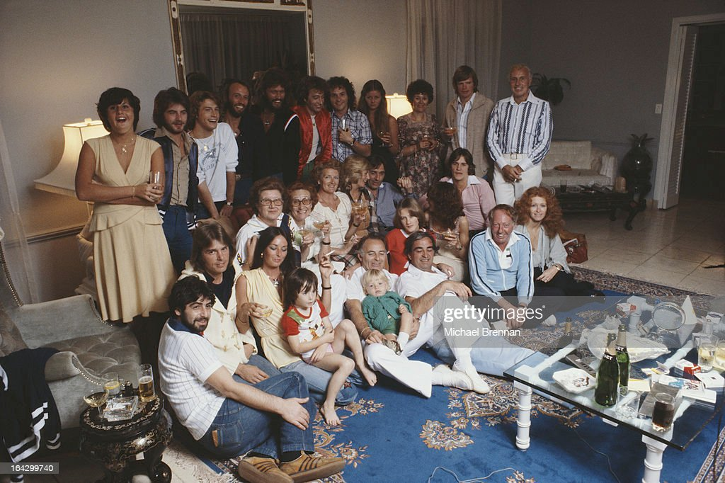 The Bee Gees at home in Miami, Florida, with their friends and family, March 1978. Pictured are Robin, Maurice and Barry Gibb with their brother Andy Gibb (1958 - 1988, front left), manager Robert Stigwood, and Barry's wife Linda, March 1978.