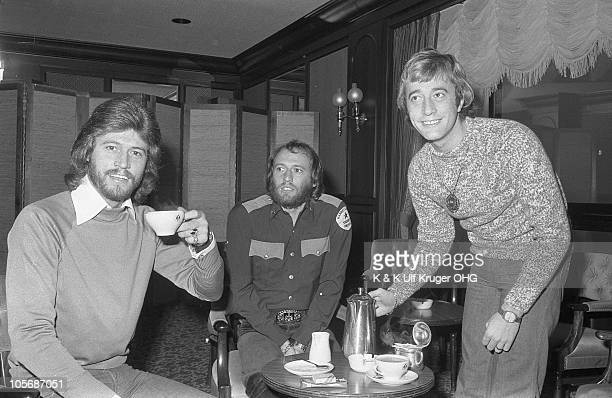 The Bee Gees LR Barry Gibb Maurice Gibb and Robin Gibb drink cups of tea during a press reception circa 1975 in Hamburg Germany