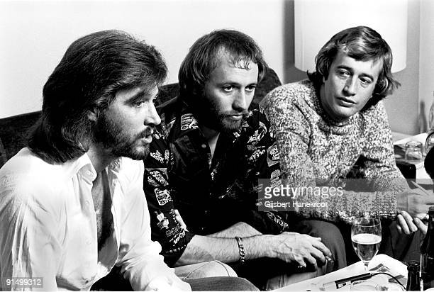 The Bee Gees posed sitting at a table in Amsterdam in 1975 LR Barry Gibb Maurice Gibb Robin Gibb