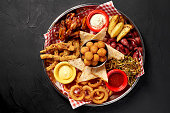 The beer plate with spicy chicken wings, calamari rings, fries onion rings, cheese balls, breaded, tartar sauce and garlic. Food and beverages concept. Still life. Copy space. Flat lay