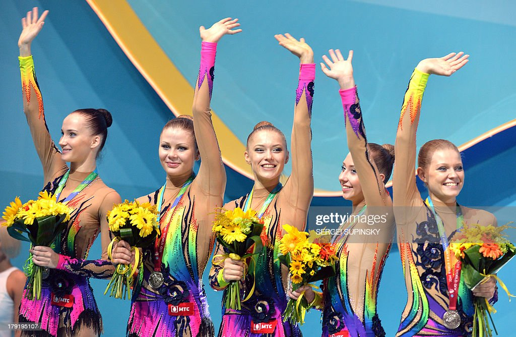 The Belarusian team waves on the podium after winning silver in the three balls two ribbons final during the 32nd Rhythmic Gymnastics World Championships in Kiev on September 1, 2013.