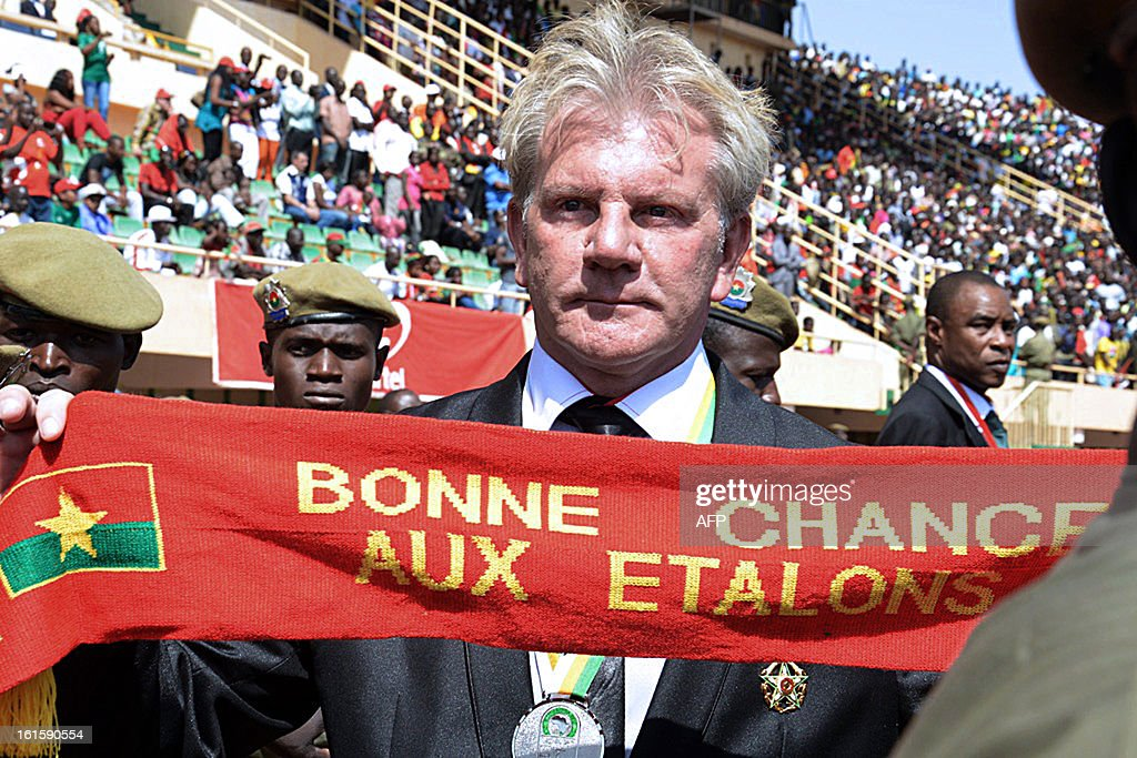 The Belgian coach of the Stallions (Burkina Faso's national football team) Belgium's Paul Put holds a scarf reading 'Good Luck to the Stallions' on February 12, 2013 during celebrations attended by some 40,000 people at the Stade du 4-août in Ouagadougou, two days after their first ever final in an Africa Cup of Nations tournament.